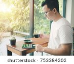asian man sitting in a coffee... | Shutterstock . vector #753384202