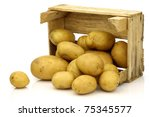 freshly harvested potatoes coming from a wooden box on a white background - stock photo