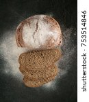 Small photo of Sliced homemade sourdough rye bread with rye flour on black textured background. Top view or flat-lay. Low key