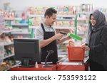 male shopkeeper scanning... | Shutterstock . vector #753593122