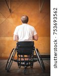 Small photo of Portrait of cripple basketball player in wheelchair on open gaming ground.