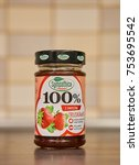 Small photo of POZNAN, POLAND - NOVEMBER 12, 2017: Sympathica 100 percent strawberry marmalade in a glass jar on wooden table