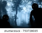 Stock photo two monsters with green eyes in misty forest landscape photo toned in blue color 753728035