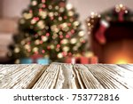 Small photo of A table with space for your advertisement. Christmas tree with lights. House Interior.