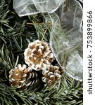 Small photo of Winter background: snowy fir tree with fir-cone and decoration white stripe. Traditional New Year and Christmas motive for greeting card. Artistic retouching.