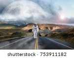 Small photo of An astronaut just landed from space, on the new planet, walks in the middle of a road to explore the new world and live there. Concept of: success road, dreams, astronaut, inspiration.