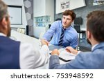 Small photo of Portrait of young successful businessman shaking hands with partners at meeting table in board room greeting each other before negotiations