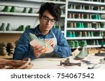 young cobbler measuring shoe by ... | Shutterstock . vector #754067542