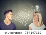 Small photo of Language barrier concept. Handsome man talking to an attractive young woman with question mark