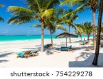 beach beds among palm trees at... | Shutterstock . vector #754229278