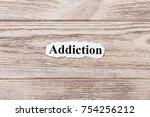 Small photo of Addiction of the word on paper. concept. Words of Addiction on a wooden background.