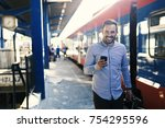 handsome young man at the train ... | Shutterstock . vector #754295596