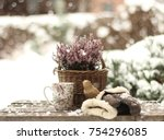 Heather in a basket ,mittens and a mug of tea in the winter garden