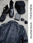 Small photo of Set of back black leather punk jacket with punk shoes, purse, sunglasses-gray background