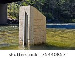 A water gage on two sides of a concrete block in a river.  Used by kayaks and rafters. - stock photo