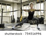 Small photo of Athletic girl is training with a TRX Rip Trainer in the gym on the windows background. She wears a pants with patterns, black sleeveless and light sneakers. Woman looks forward with parted lips.