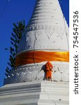 """Small photo of A monk standing on a """"Gong Moo"""" pagoda,Mae Hong Son,Thailand"""