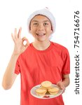Teenage boy with a plate of mince pies giving positive gestures - stock photo
