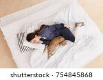 Stock photo young girl in a blue pajamas sleeps on a big white bed with a red cat healthy day sleep top view 754845868