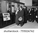 Small photo of Couples lined up in New York City to apply for their $1.00 marriage licenses, 1915-20. The couple at the Marriage Bureau clerk's window swear to the truthfulness of their application