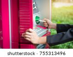 Small photo of Close up woman hand inserting card into ATM. Inserting credit card into bank machine to withdraw money.