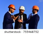 Small photo of Architects hold clip folder. Men with beard and astonished faces have dispute. Managers wear smart suits, ties and hardhats on blue sky background. Building and engineering concept.