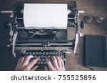 Small photo of top view of man using vintage manual typewriter on rustic wooden table