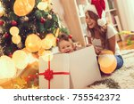 Young mother sitting on the floor next to a Christmas tree, playing with her baby girl who is jumping out of a present box
