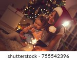 Beautiful young mother and daughter sitting on the floor next to a Christmas tree, playing with sparklers and eating chocolate. Focus on the baby girl