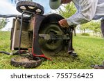 man cleaning lawn mower blade. | Shutterstock . vector #755756425