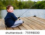 Boy Smiles While Fishing From...