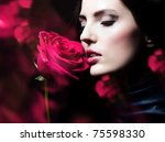 close-up portrait of beautiful brunette woman with red rose - stock photo