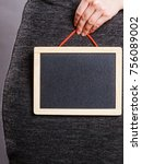Small photo of Feminine body problems concept. Woman holding blank black board on crotch, grey background.