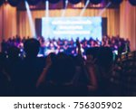 Small photo of Blurred Christian Congregation Worship God together in Church hall in front of music stage and light effected.
