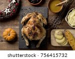 Small photo of high-angle shot of a roast turkey placed on a rustic wooden table next to some bowls with gravy, mashed potatoes, blueberry jam, some slices of roasted potato or a roasted corn