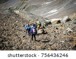 Small photo of A group of hiking tourists descends from a mountain pass along a steep stony slope. The weather facilitates complex movement in the highland area.
