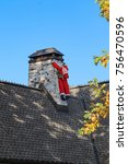 Small photo of Deflated Blow up Santa tied to chimney looking limp and like he is trying to hang on - funny - with fall leaves and light bulbs on roof line - early decorating for Christmas
