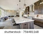 Stock photo luxury kitchen accented with large granite kitchen island taupe tile backsplash natural brown 756481168