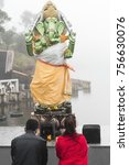 Small photo of A kneeling man and woman pray in front of a Hindu deity, Grand Bassin Mauritius