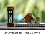 Small photo of close up hourglass, stack of coins, notebook and toy house on old wood table, saving money for building and manage time for success business concept