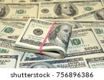Small photo of A stack of one hundred dollars on 100 dollars notes background