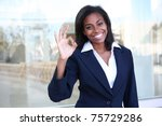 A pretty african american business woman signaling success at office - stock photo