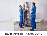 two young male movers packing... | Shutterstock . vector #757879096