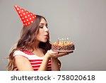 Young Woman Blowing Out Candles ...