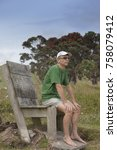 Small photo of Man sitting outdoors on big old wooden chair in?? Whananaki, Northland, North Island, New Zealand