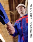 Small photo of Two workers in a construction helmet shake hands. Business deal, conclusion of a contract