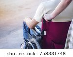 woman pushing wheelchair with... | Shutterstock . vector #758331748