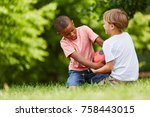 Small photo of Two boys scuffle for soccer ball in match in the park