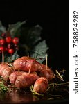 Small photo of Festive cocktail sausages wrapped in crispy smoked bacon commonly known as 'Pigs in Blankets' shot against a festive dark background with creative lighting with generous accommodation for copy space.