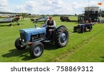 Small photo of Old Warden airfield, Bedfordshire, UK - 08/06/17: 1963 Fordson Super Dexta tractor towing 1926 Jowett Type C, passing 1933 Avro Tutor at Shuttleworth Collection's 2017 Edwardian Pagent.
